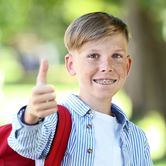 Young boy with braces smiling and giving thumbs up
