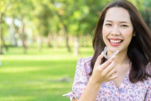 Woman smiles as she holds Invisalign in Dayville