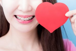 Closeup of smile with braces in Dayville and paper heart