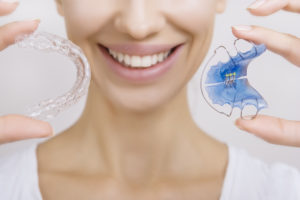 Closeup of smiling woman holding a traditional retainer and modern retainer